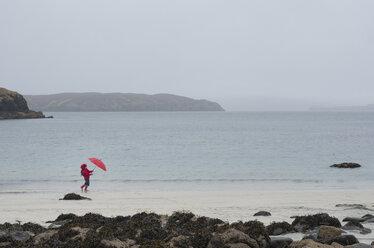 UK, Scotland, Isle of Skye, walking girl with umbrella at rainy and stormy beach - JBF000255