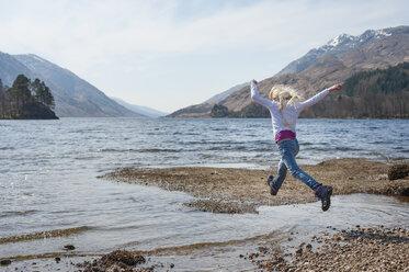 UK, Scotland, Scottish Highlands, Loch Shiel, girl jumping over water - JBF000258