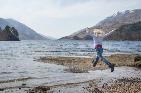 UK, Scotland, Scottish Highlands, Loch Shiel, girl jumping over water - JBF000258