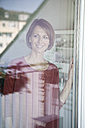 Smiling woman looking out of window - RBF003572