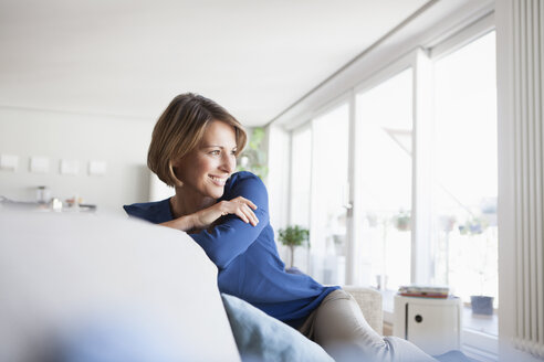 Smiling woman at home sitting on couch - RBF003575