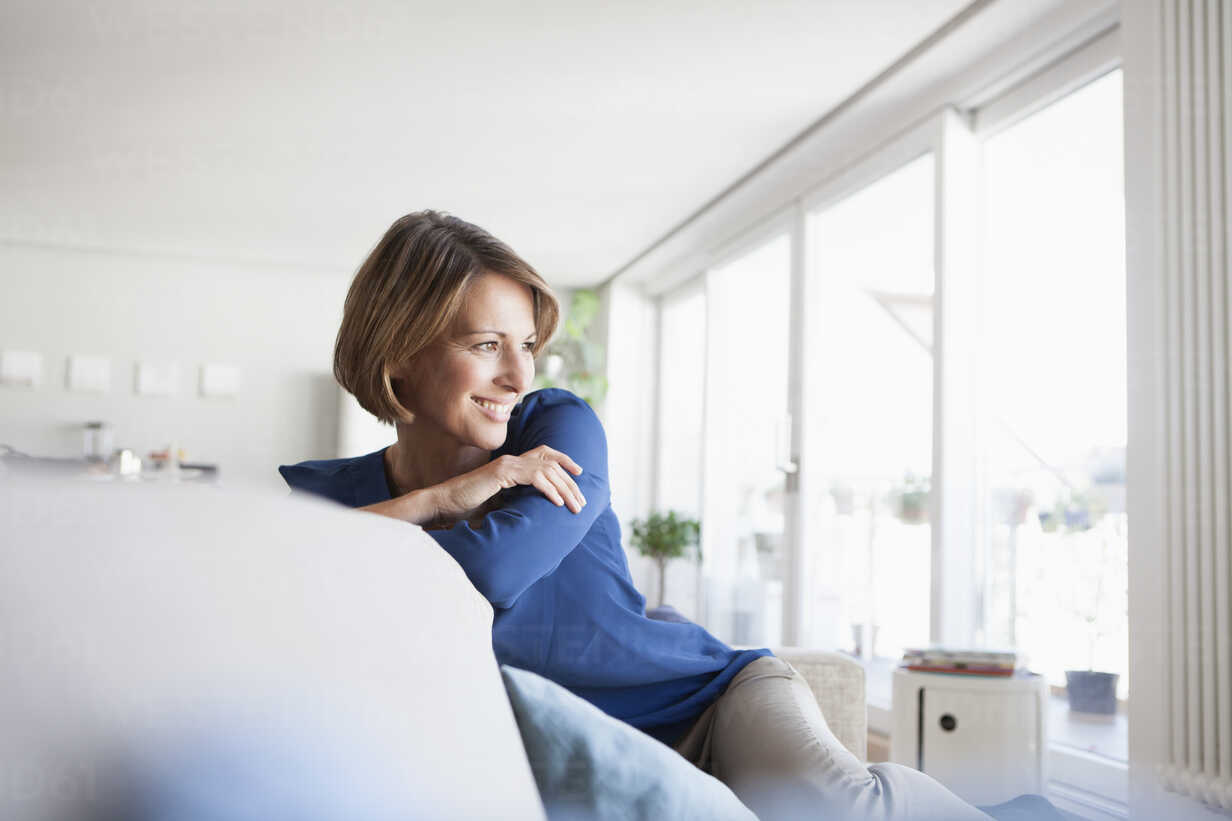Smiling woman at home sitting on couch - RBF003575 - Rainer Berg/Westend61