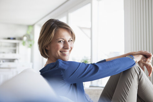 Smiling woman at home sitting on couch - RBF003578