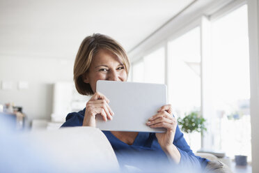 Happy woman at home holding digital tablet - RBF003581