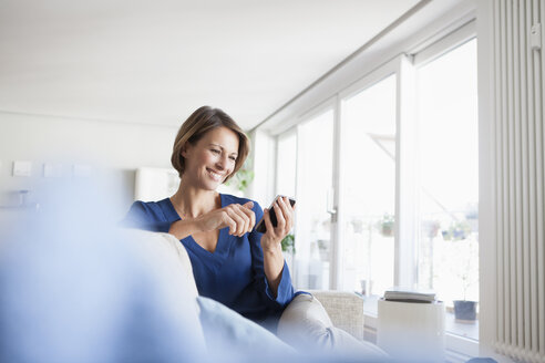 Smiling woman at home sitting on couch looking at cell phone - RBF003584