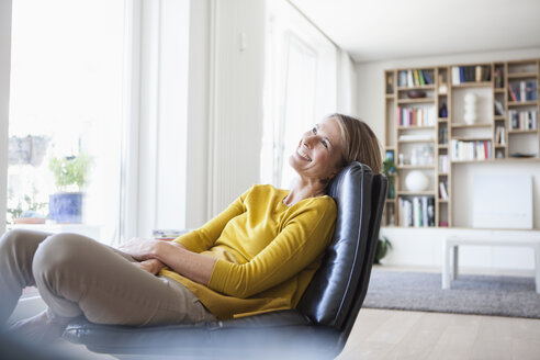 Relaxed woman at home sitting on leather chair - RBF003599