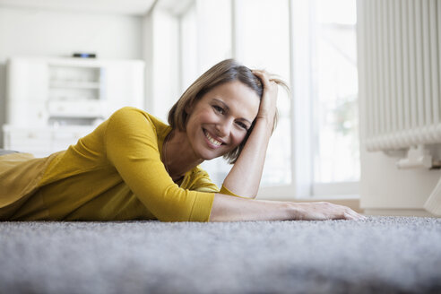 Portrait of relaxed woman at home lying on floor - RBF003608