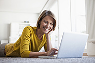 Relaxed woman at home lying on floor using laptop - RBF003611