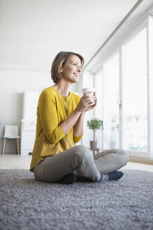 Relaxed woman at home sitting on floor holding cup - RBF003614
