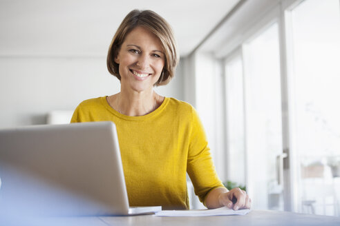 Portrait of smiling woman at home using laptop - RBF003623