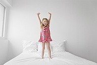 Little girl standing on a bed with arms up - LITF000166