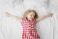 Portrait of smiling little girl lying on a bed with outstretched arms - LITF000175