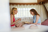 Two female friends sitting in a caravan having a good time - HAPF000048