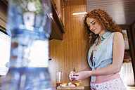 Smiling young woman standing in a  caravan cutting fruits - HAPF000051