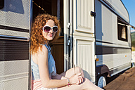 Portrait of smiling young woman sitting at entrance of caravan - HAPF000054