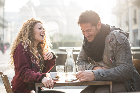 Italy, Milan, laughing couple sitting at sidewalk cafe having fun - OIPF000009