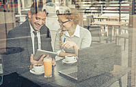 Two smiling business partners sitting in a coffee shop with digital tablet and laptop - OIPF000021