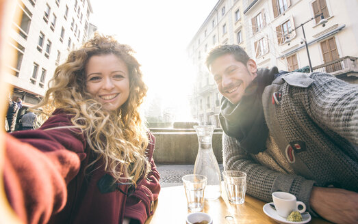 Italy, Milan, couple sitting at sidewalk cafe taking selfies - OIPF000030
