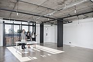 Businesspeople standing and talking in new open office - ZEF007536