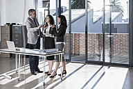 Businesspeople standing and talking in new open office - ZEF007539