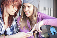 Two friends with skateboard listening to music - ZEF007575