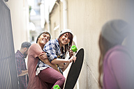 Friends with skateboard having fun in a passageway - ZEF007590