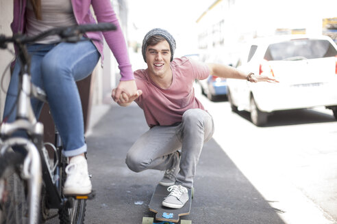 Teenage girl on bicycle pushing young man on skateboard - ZEF007593