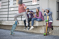 Young man with friends doing a skateboard trick - ZEF007605