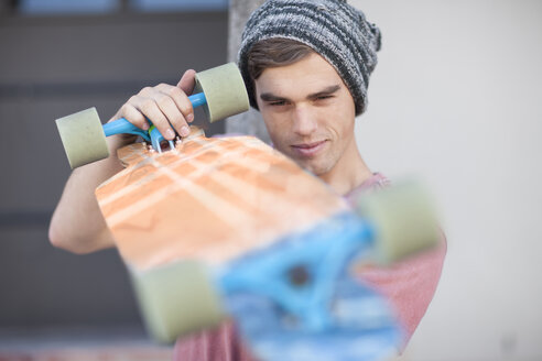 Young man scrutinizing his skateboard - ZEF007617