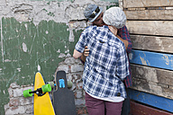 Young couple with skateboard hugging and kissing - ZEF007629