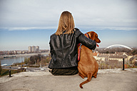 Serbia, Novi Sad, back view of  young woman sitting beside her  dog looking at view - ZEDF000033