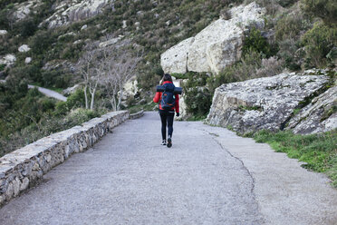 Spain, Catalunya, Girona, female hiker walking on country road - EBSF001161