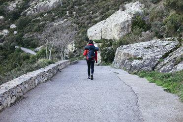 Spain, Catalunya, Girona, female hiker walking on country road - EBSF001161
