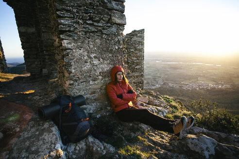 Spain, Catalunya, Girona, female hiker resting at stone structure - EBSF001167