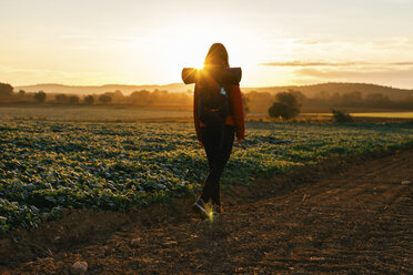 Spain, Catalunya, Girona, woman hiking on field path at sunrise - EBSF001179