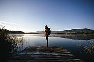 Spain, Catalunya, Girona, female hiker on jetty at a lake enjoying the nature - EBSF001185