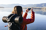 Spain, Catalunya, Girona, female hiker taking a cell phone picture at a lake - EBSF001188