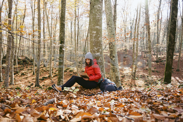 Spain, Catalunya, Girona, female hiker sitting in the woods reading book - EBSF001200 - Bonninstudio/Westend61