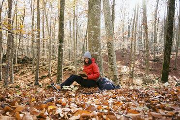 Spain, Catalunya, Girona, female hiker sitting in the woods reading book - EBSF001200