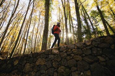Spain, Catalunya, Girona, female hiker walking on stone wall in the woods - EBSF001203