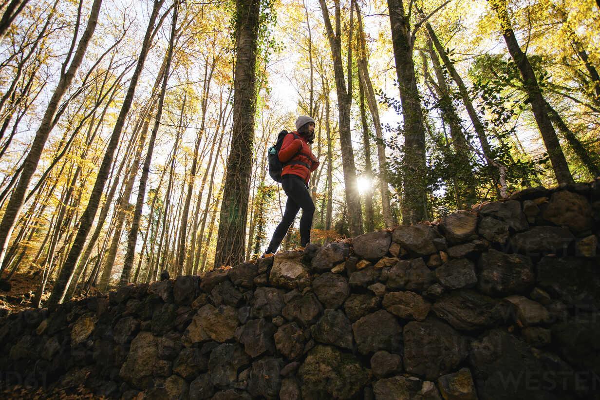 Spain, Catalunya, Girona, female hiker walking on stone wall in the woods - EBSF001203 - Bonninstudio/Westend61
