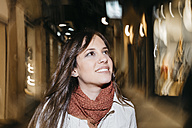 Spain, Reus, portrait of smiling young woman walking through the city at night - JRFF000251