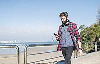 Spain, La Coruna, hipster with headphones looking at his smartphone - RAEF000722