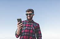 Spain, La Coruna, portrait of smiling hipster with sunglasses looking at his phablet in front of blue sky - RAEF000728