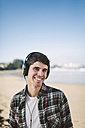 Spain, La Coruna, portrait of smiling man with headphones on the beach - RAEF000731