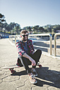 Spain, La Coruna, portrait of smiling hipster wearing sunglasses sitting on his longboard - RAEF000734