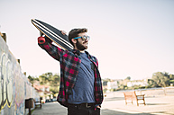 Spain, La Coruna, smiling hipster wearing sunglasses holding  longboard on his shoulder - RAEF000740