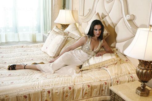 Woman wearing fashionable dress lying on hotel bed - TM000088