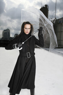 Germany, Munich, portrait of woman wearing black clothes standing on a roof with transparent umbrella - TMF000091