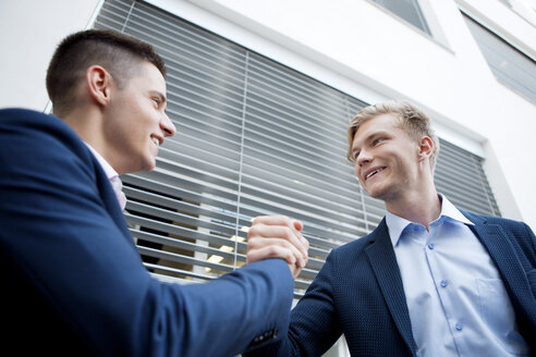 Two smiling businessmen shaking hands outdoors - WESTF021597